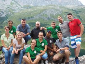 Gruppenbild von unserem internationalen Hüttenteam draußen vor dem Formarinsee