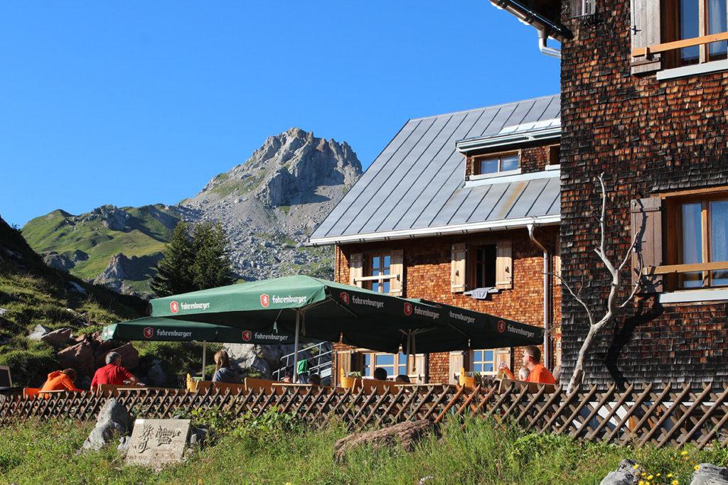 Blick auf die schöne Terrasse unserer Alpenvereinshütte, von der aus man beim Essen und Trinken die Aussicht auf die Umgebung genießen kann